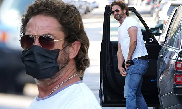 Gerard Butler wears a mask during a solo outing… following split from girlfriend Morgan Brown